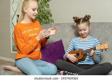 Two sisters sitting on ground floor,play ukulele with interested feeling,doing activity together