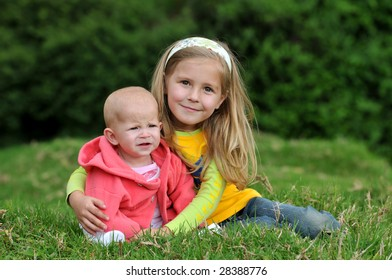 Two sisters are sitting on the lawn