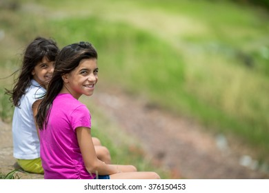 Two sisters sitting outdoors, blurry background
