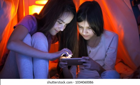 Two sisters with smartphone in bedroom at night - Shutterstock ID 1034060086
