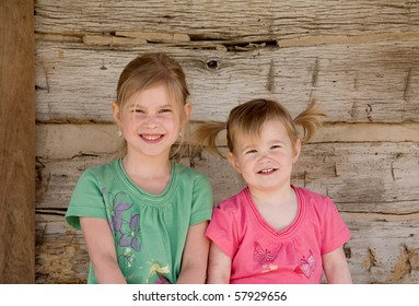 Two Sisters Smiling Big in Front of Home