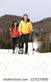 Two sisters snowshoeing in park with cottage behind