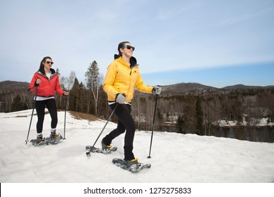Two sisters snowshoeing in park together happily