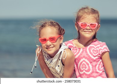 two sisters standing on the beach at the day time