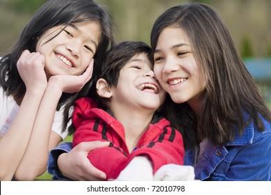 Deux soeurs et leur petit frère handicapé assis ensemble dans le parc, partie métis d'origine thaïlandaise et scandinave.