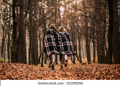 two sisters are twins in the autumn woods covered with blankets
