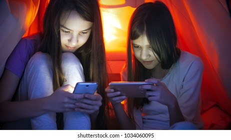 Two sisters using mobile phones at night before going to sleep - Shutterstock ID 1034060095