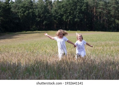 Two sisters are walking in the field, they are wearing white clothes. You enjoy the breadth of the field and the freedom