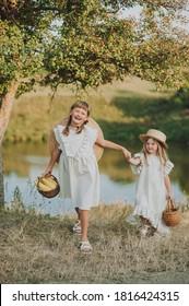 deux soeurs marchent près du lac et tiennent des paniers avec des fruits et du maïs