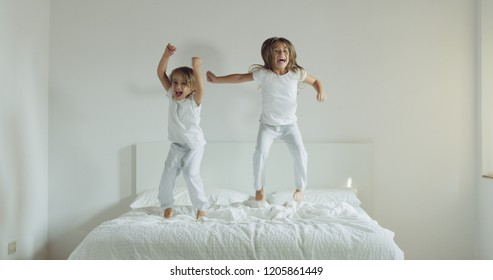 Two sisters, wearing white pajamas, jump on the bed and have fun. Concept of youth, wellness and health, happiness and freedom.