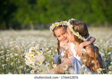 Zwei Schwestern in weißen Kleider und Kränze von Gänseblümchen in einem Sommerfeld von Gänseblümchen. Mädchen auf einem Feld mit Blumen. Kamillenfeld.