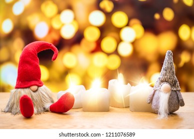 Two sitting christmas elfs with bokeh lights in background surrounded by four ignited advent candles