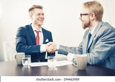 Two Sitting Men Handshaking