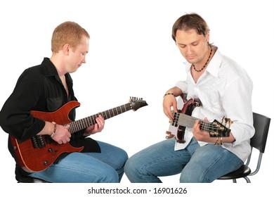 Two sitting men play on guitars