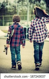 two skater boys walking towards half pipe,vintage effect added