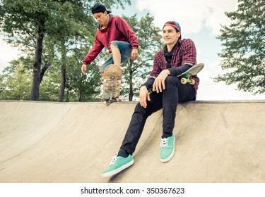 Two skaters practicing at the skate park. Young boys having fun with skateboards