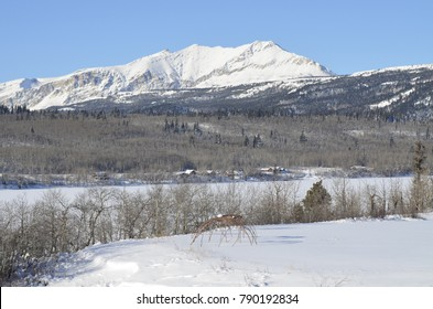 Two skeleton sweat lodges sit in a snow covered field with a magnificent mountain and lake background