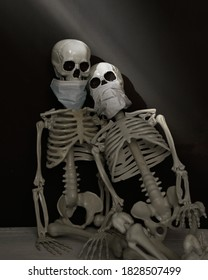 Two skeletons are wearing facial masks against a black wall with sunlight for a scary, strange halloween decoration concept.