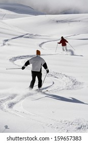 Two skiers going down a fresh powder snow slope. First area near Grindelwald, Berner Oberland, Switzerland.
