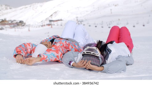Two skiers laying on the ground