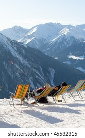 Two skiers relax with a beer in reclining chairs in the sun on top of an Austrian mountain covered with snow