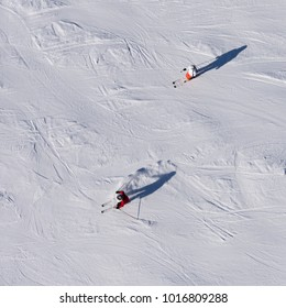 Two skiers skiing downhill on a piste