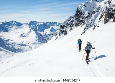 Two skiers skinning uphill on a hot sunny day in the Alaska backcountry of the Talkeetna Mountains.