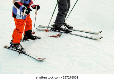 Two skiers and skis close-up.
