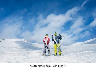 Two skiers stand in the background of snow mountains. man and girl.