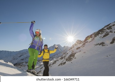 two skiiers beckon and have fun