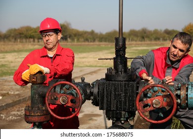 Two Skilled Oil and Gas Engineers in Action at Oil Well.Two oil and gas engineers working on oil rig equipment.