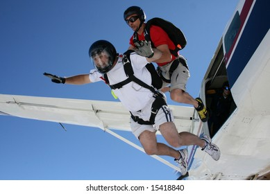 Two skydivers exit an airplane