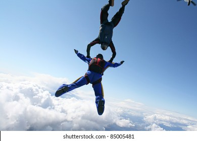 Two skydivers exit an airplane high up in the air