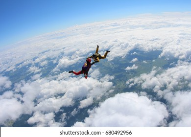 Two skydivers are falling above the white clouds in the sky.