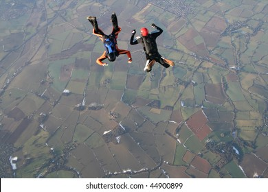 Two skydivers in free fall with snow in the background
