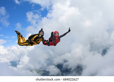Two skydivers are having fun near the big white clouds.