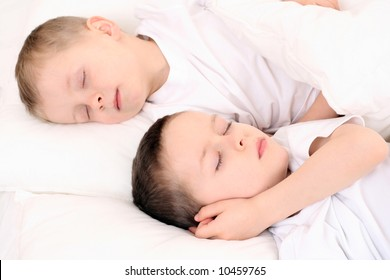 two sleeping children in white bedclothes