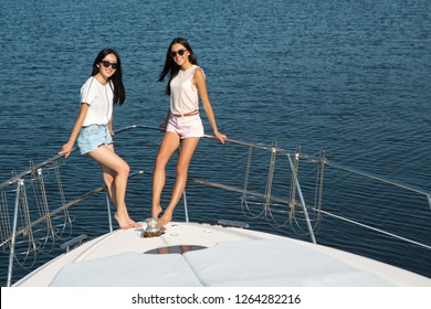 Two slender and beautiful girls standing on boat bow and posing at camera. Pretty brunettes with long legs and bronze sunburn wearing white clothes and sunglasses. Sea on background.