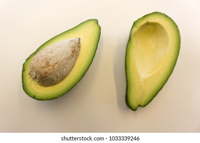 Two slices of avocado isolated on the white background. One slice with core. Design element for product label