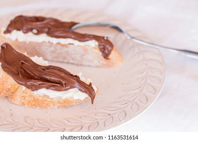 Two slices of bread with mascarpone cheese and chocolate cream.