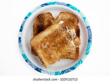 Two slices of buttered toast on a paper dish against a white background.