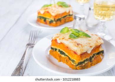 Two Slices of Creamy Classic Veggie Pumpkin and Spinach Lasagne on a White Wooden Table
