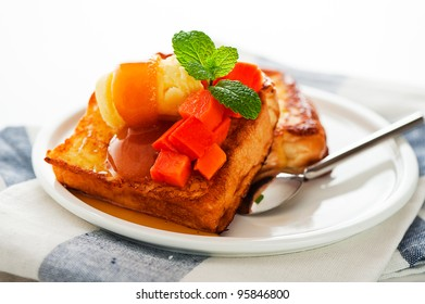 Two slices of french toast with papaya, vanilla ice cream, caramel sauce and mint leaf on a white background as a studio shoot