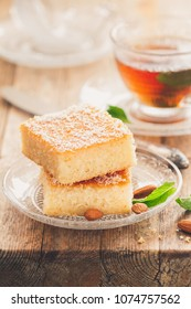 Two slices of homemade semolina cake on a wood vintage rustic table background with mint tea