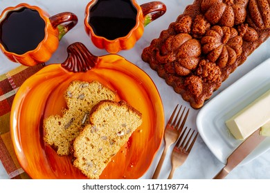 Two slices of pecan pumpkin bread sitting on pumpkin plate with two cups of coffee and a whole loaf of bread made in decorative pan