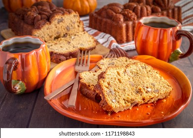 Two slices of pecan pumpkin bread slices sitting on pumpkin plate with two cups of coffee and fresh baked loaves of bread on wooden table