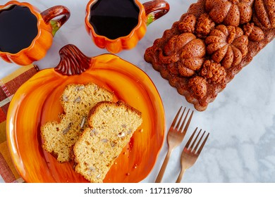 Two slices of pumpkin bread sitting on pumpkin plate with two cups of coffee and a whole loaf of bread made in decorative pan with space for text