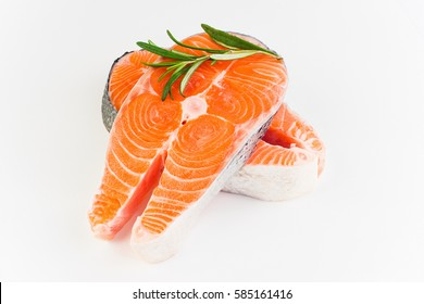 Two slices of red fish with rosemary  on a white plastic background. Closeup. on a white plastic cutting board