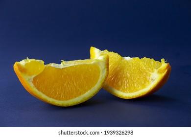 Two slices of sweet orange subject photography. Orange still life on dark blue background macro photography. Juicy citrus fruit close-up photography.