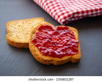 Two slices of toast with raspberry jam on a slate plate